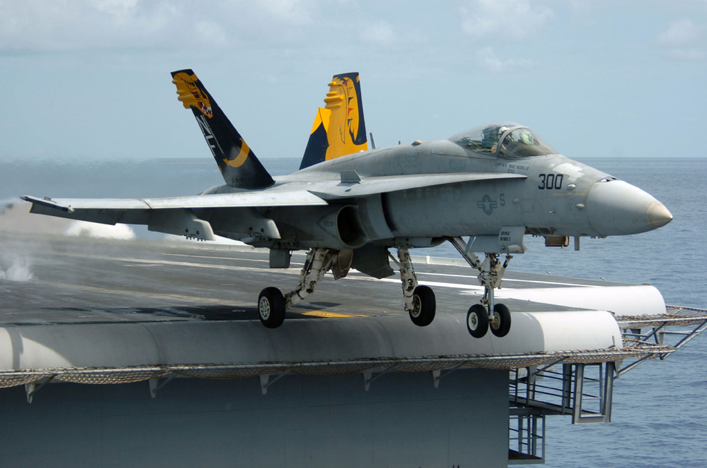 An F/A-18C Hornet launches from the flight deck of the aircraft carrier USS Kitty Hawk